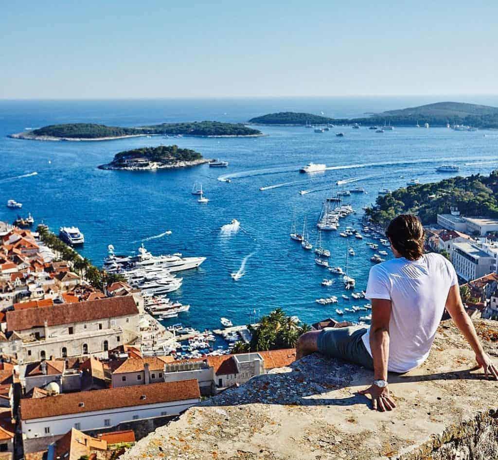Man looking over Hvar harbour from the Hvar Fortress