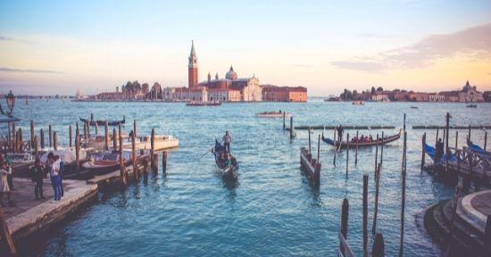 A gondola with passengers in front of the Rialto Bridge in Venice
