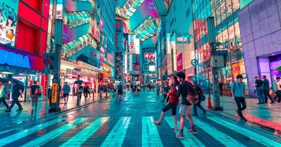 Two young Japanese people crossing a busy road in Tokyo at night